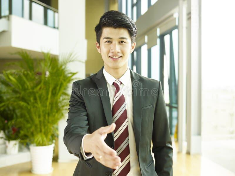 Hombre de negocios asiático joven que alcanza hacia fuera para el apretón de manos imagenes de archivo
