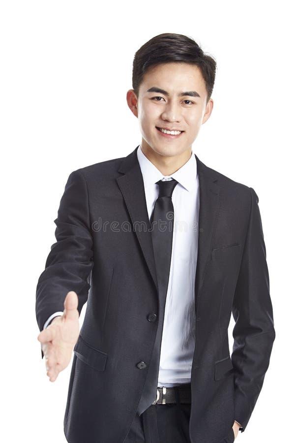 Hombre de negocios asiático joven que alcanza hacia fuera para un apretón de manos imagenes de archivo