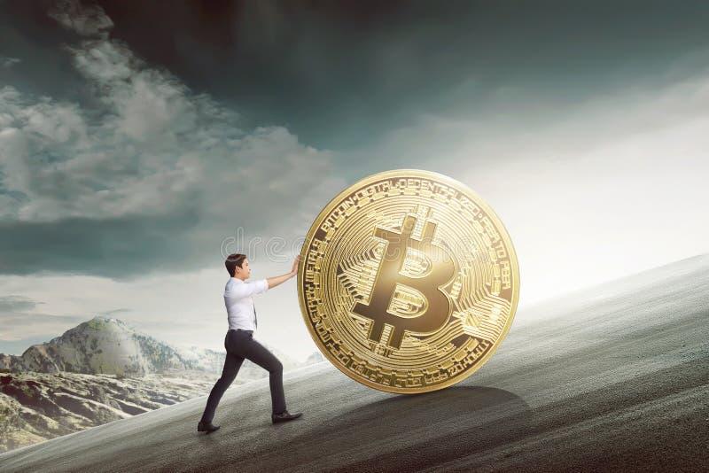 Hombre de negocios asiático joven que empuja el bitcoin de oro que sube la colina imagen de archivo libre de regalías