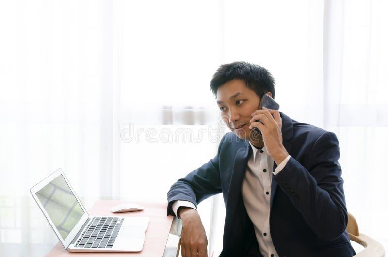Hombre de negocios asiático joven que habla en el teléfono, mirando el ordenador y pensando para tomar la decisión para un trato imágenes de archivo libres de regalías