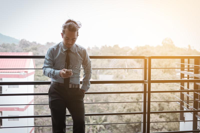Hombre de negocios asiático joven que habla en el teléfono y la felicidad para el trabajo fotos de archivo