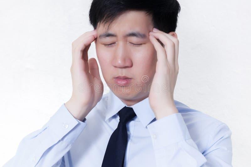 Hombre de negocios asiático joven que hace frente a problemas del dolor de cabeza/de la jaqueca en el blanco aislado imagen de archivo