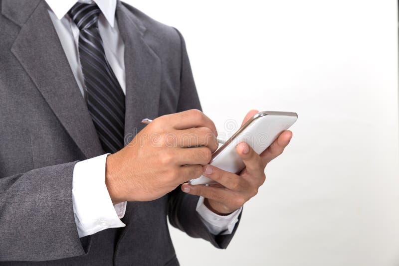 hombre de negocios asiático joven que lleva el traje gris usando pho elegante móvil imagen de archivo