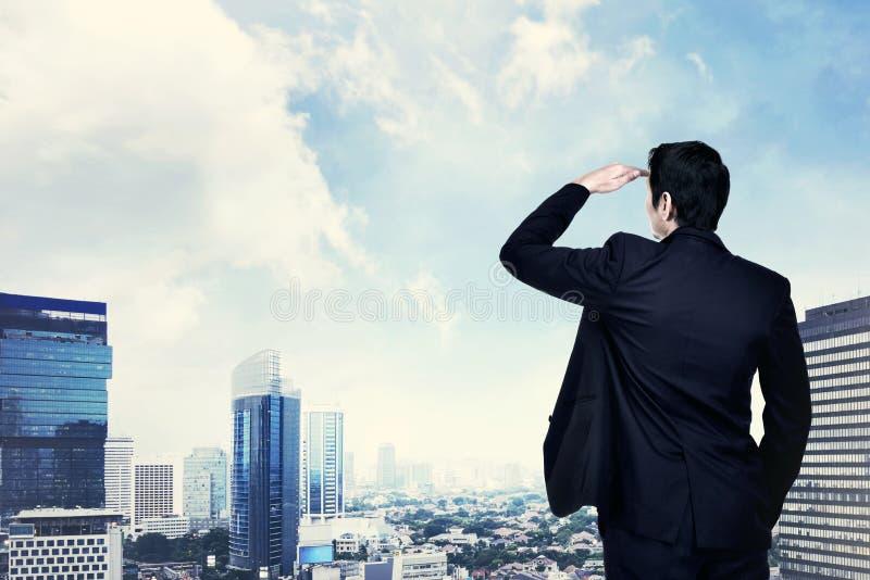 Hombre de negocios asiático joven que mira el paisaje urbano fotografía de archivo