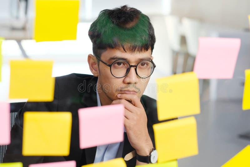 Hombre de negocios asiático joven que piensa mientras que lee las notas pegajosas en la oficina, negocio brainstroming ideas de c imagenes de archivo