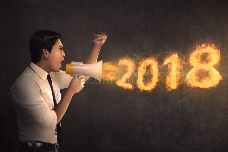 Hombre de negocios asiático joven que sostiene el megáfono y que grita 2018 en f imagenes de archivo
