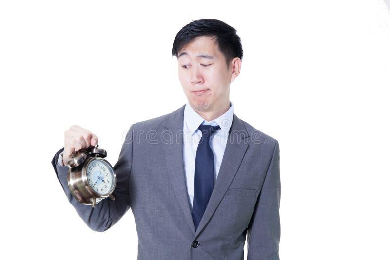 Hombre de negocios asiático joven que sostiene un reloj en la expresión desagradable de la cara - concepto del negocio y del tiem foto de archivo