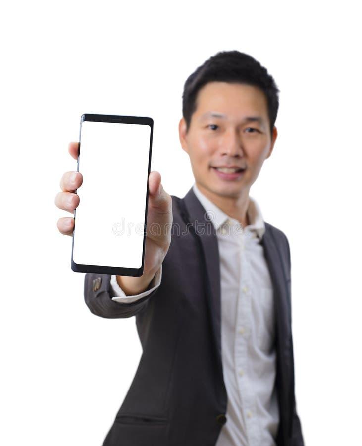 Hombre de negocios asiático joven que sostiene un smartphone con la pantalla en blanco en traje negro imágenes de archivo libres de regalías