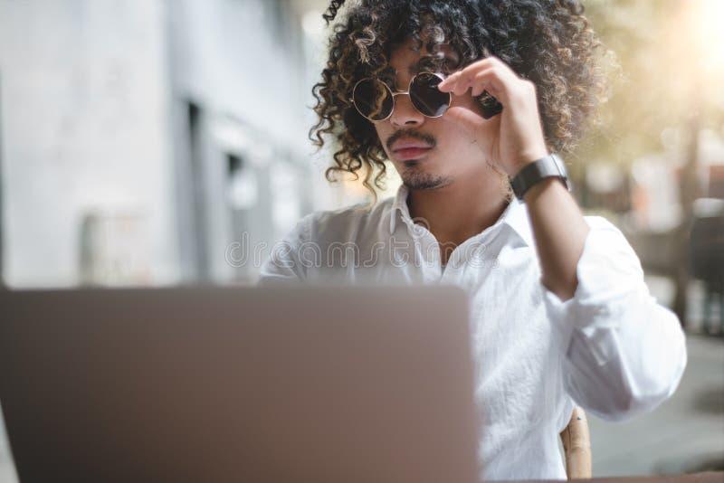 Hombre de negocios asiático joven que trabaja con el ordenador portátil al aire libre fotografía de archivo