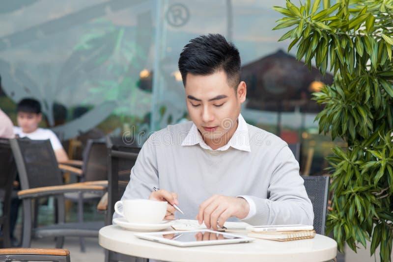Hombre de negocios asiático joven que trabaja con los documentos en el café imagen de archivo libre de regalías