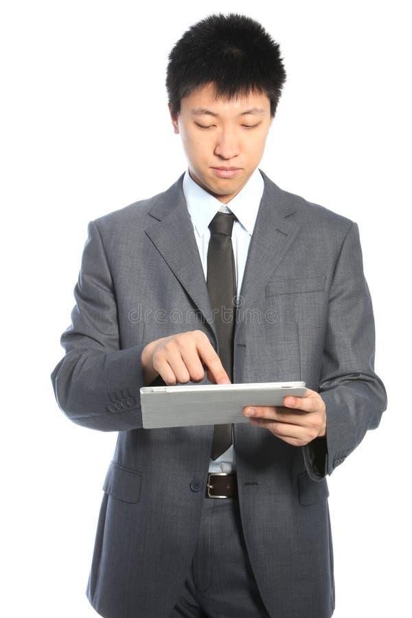 Hombre de negocios asiático joven que trabaja en una tablilla de la PC imagen de archivo