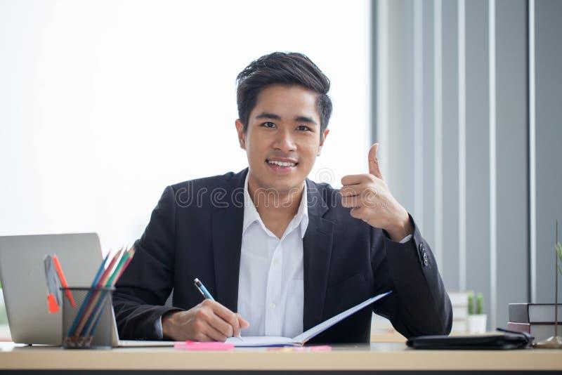 Hombre de negocios asiático joven sonriente que trabaja con el cuaderno en el escritorio y el pulgar de la demostración para arri fotografía de archivo libre de regalías