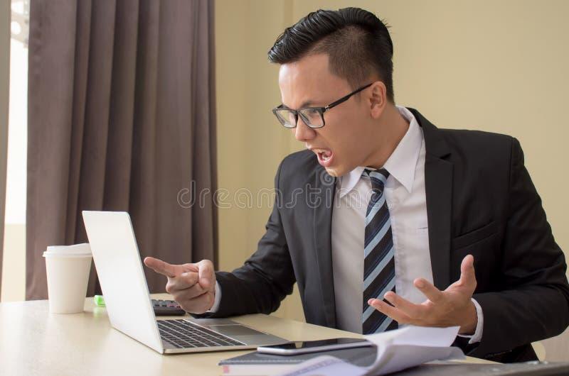 Hombre de negocios asiático joven subrayado hermoso en los vidrios furiosos con el ordenador portátil fotos de archivo libres de regalías