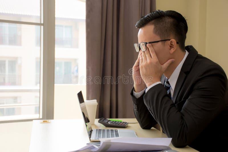 Hombre de negocios asiático joven subrayado hermoso en vidrios con el ordenador portátil fotografía de archivo libre de regalías