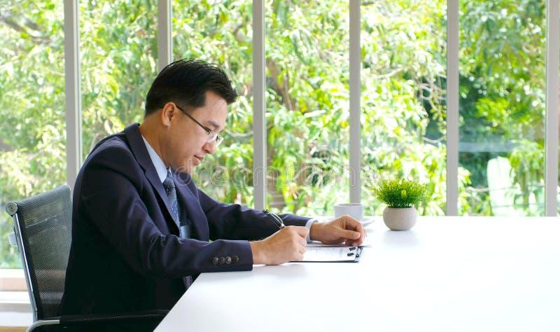 Hombre de negocios asi?tico mayor que trabaja en el documento en su escritorio de oficina, hombres de negocios, concepto de la fo imagen de archivo libre de regalías