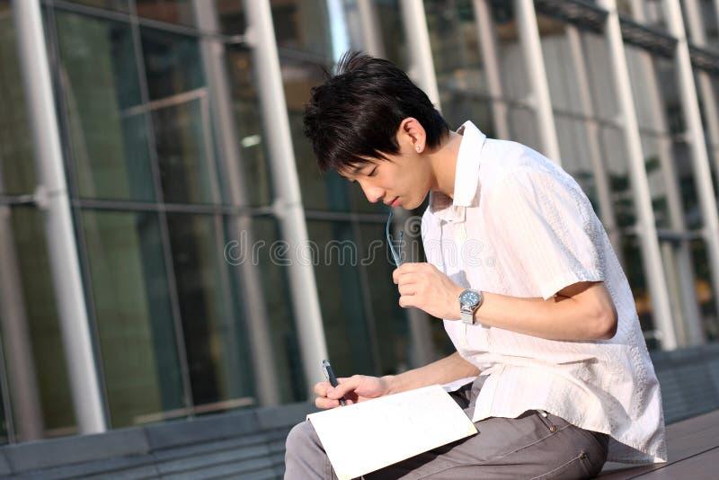 Hombre de negocios asiático ocasional texting en su libro imagen de archivo libre de regalías