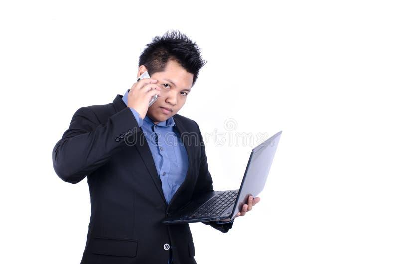 Hombre de negocios asiático ocupado que habla el teléfono elegante foto de archivo