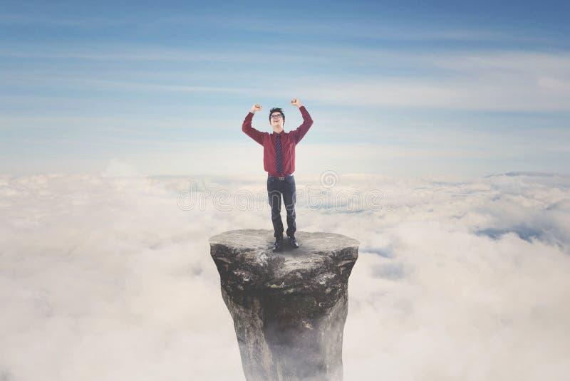 Hombre de negocios asiático que celebra su éxito en la montaña imagen de archivo