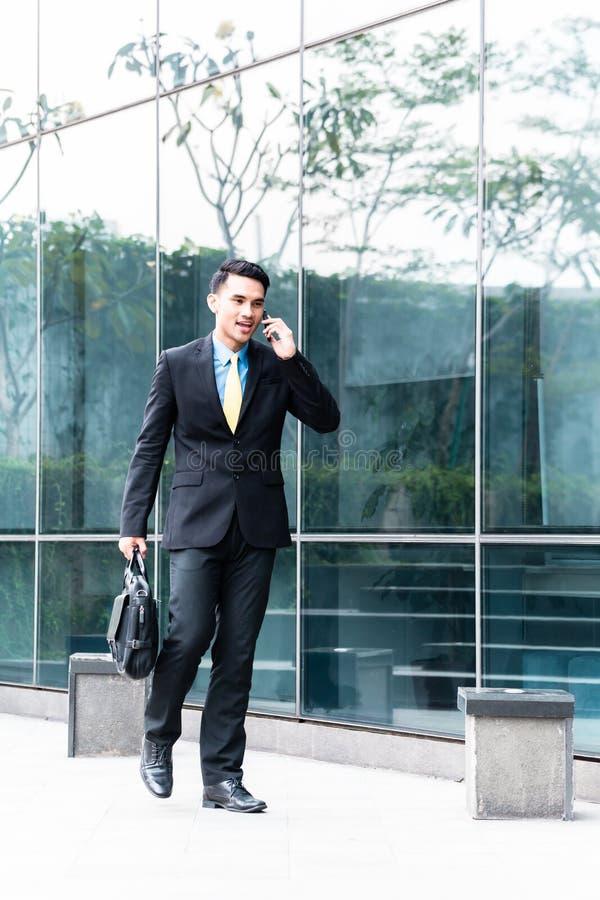 Hombre de negocios asiático que habla con el teléfono celular afuera fotos de archivo