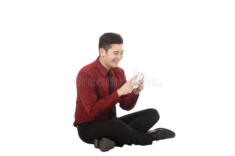 Hombre de negocios asiático que manda un SMS con el teléfono móvil y que se sienta en el piso imágenes de archivo libres de regalías