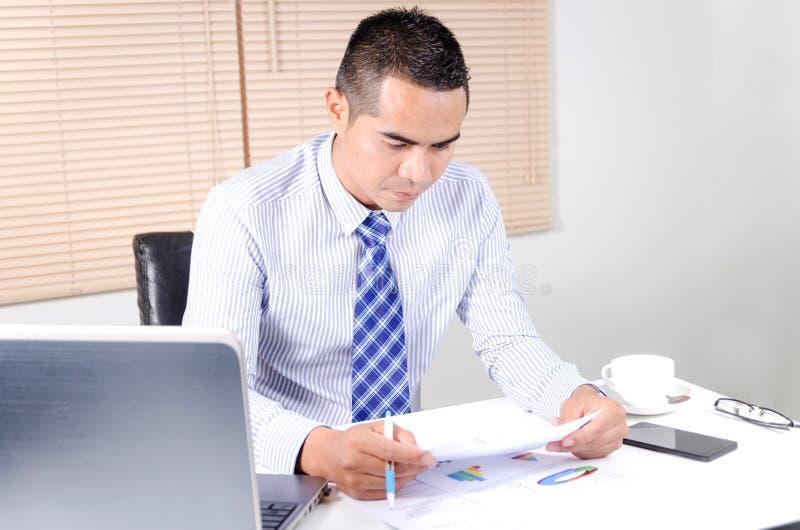 Hombre de negocios asiático que mira el documento en oficina del lugar de trabajo imagenes de archivo