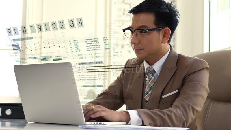 Hombre de negocios asiático que mira intenso las figuras de ventas en el ordenador foto de archivo libre de regalías