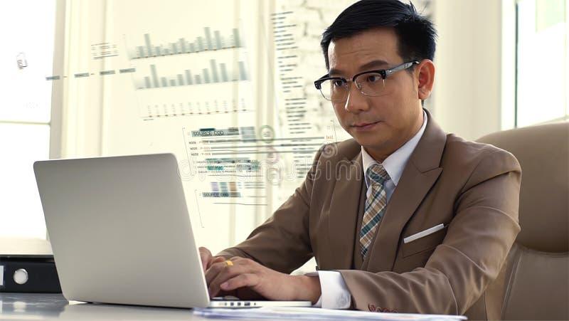 Hombre de negocios asiático que mira intenso las figuras de ventas en el ordenador foto de archivo