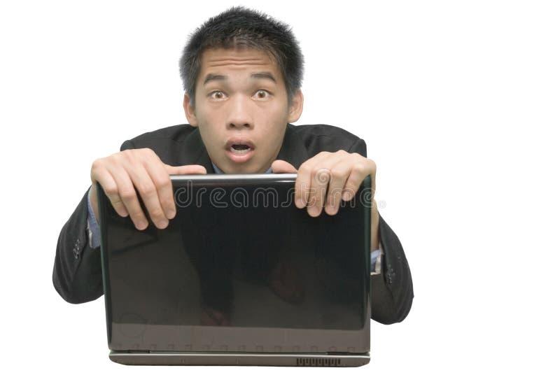 Hombre de negocios asiático que oculta detrás de la computadora portátil foto de archivo