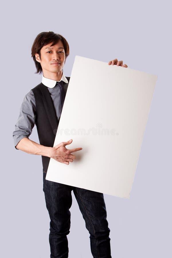 Hombre de negocios asiático que señala en la tarjeta blanca fotografía de archivo