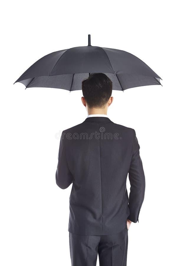 Hombre de negocios asiático que sostiene el paraguas imagenes de archivo