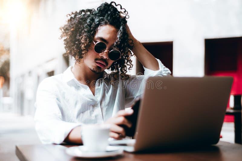 Hombre de negocios asiático rizado al aire libre con el ordenador portátil y el smartphone imágenes de archivo libres de regalías