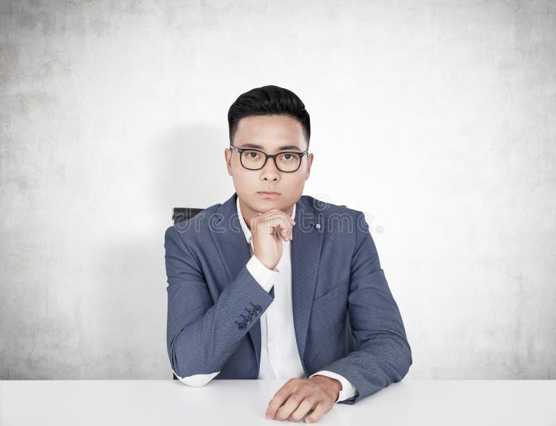 Hombre de negocios asiático serio en una tabla, concreta imagen de archivo