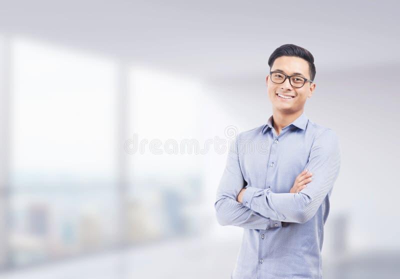 Hombre de negocios asiático sonriente en oficina borrosa fotos de archivo