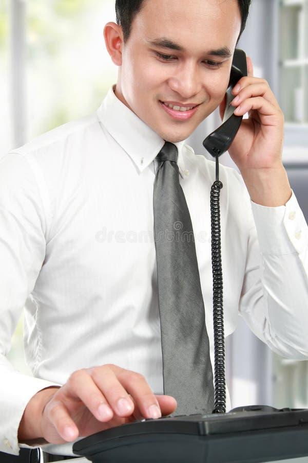 Hombre de negocios asiático sonriente que lee un informe fotos de archivo libres de regalías