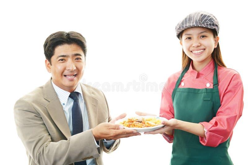 Hombre de negocios asiático sonriente y una camarera foto de archivo libre de regalías