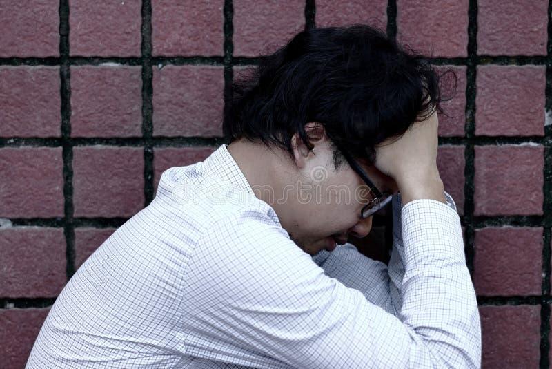 Hombre de negocios asiático subrayado para arriba frustrado del cierre en la depresión con las manos en la frente foto de archivo