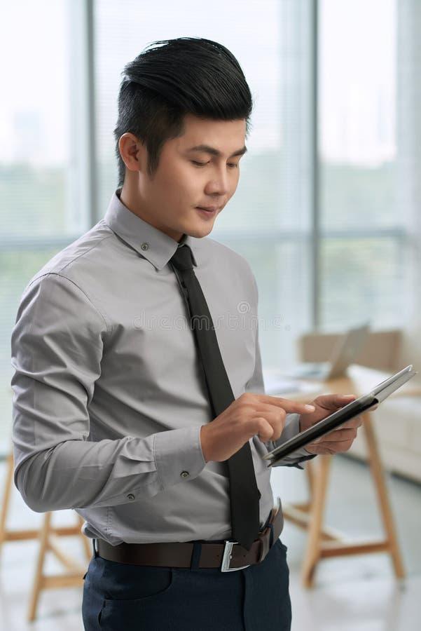 Hombre de negocios asiático usando la tableta digital foto de archivo libre de regalías