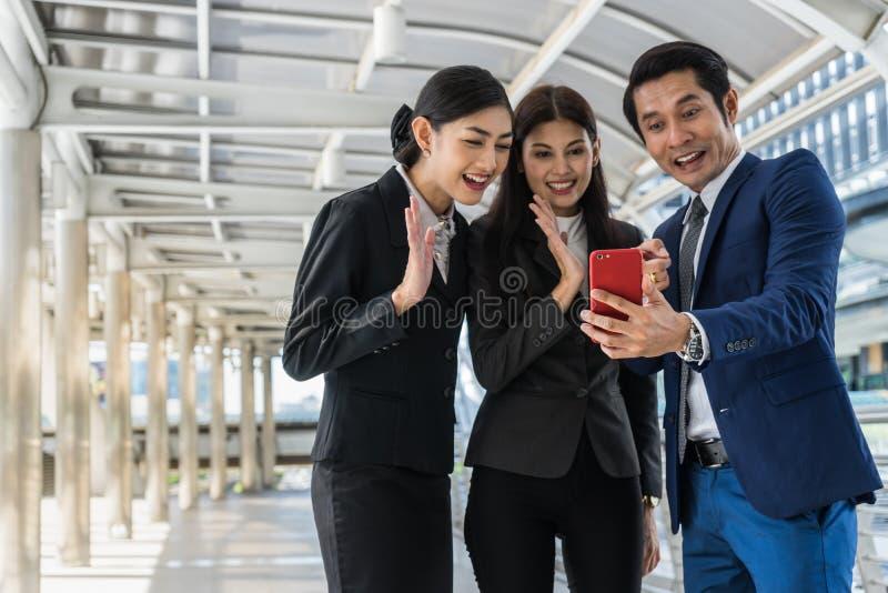 Hombre de negocios asiático y empresaria que hacen audioconferencia con alguien en el teléfono móvil fotografía de archivo libre de regalías