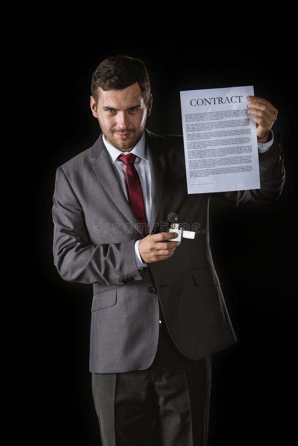Hombre de negocios astuto que sostiene el contrato y el mechero fotografía de archivo libre de regalías