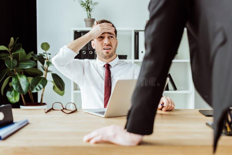 hombre de negocios asustado con el ordenador portátil que mira al jefe enojado imagen de archivo libre de regalías