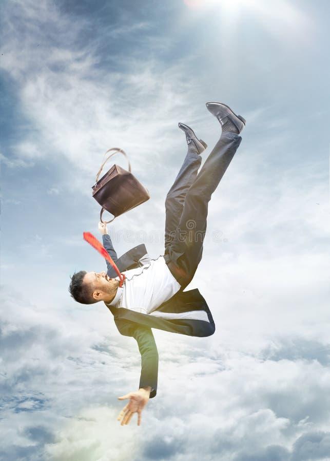 Hombre de negocios asustado que cae abajo y que grita foto de archivo