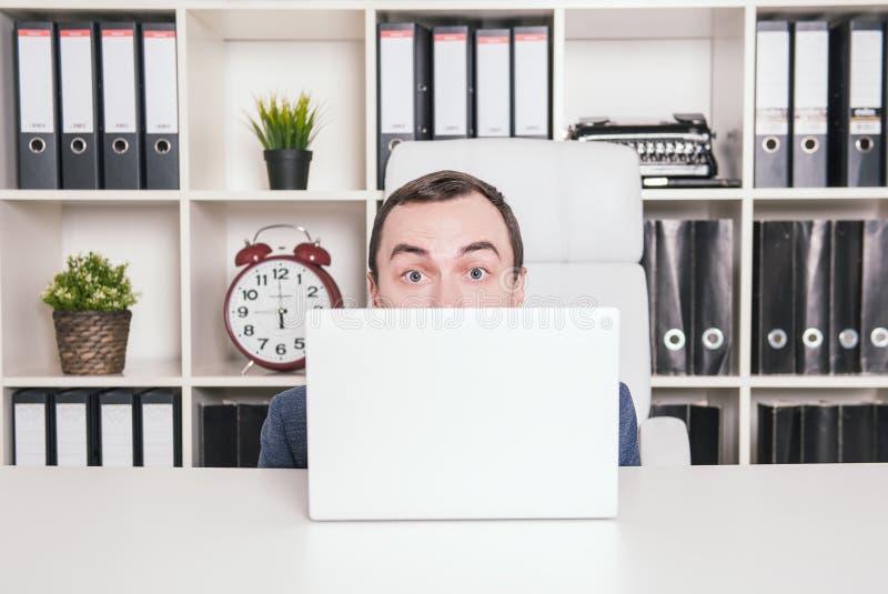 Hombre de negocios asustado que oculta detrás del ordenador portátil fotografía de archivo libre de regalías