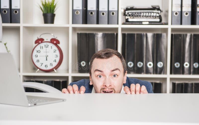Hombre de negocios asustado que oculta detrás de la tabla foto de archivo