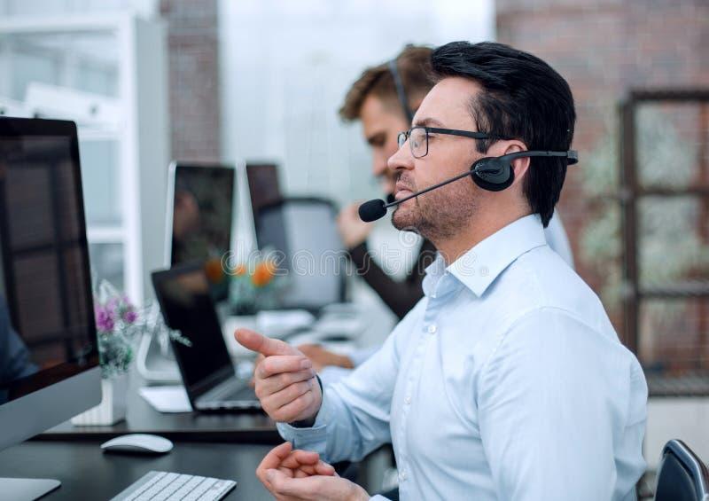 Hombre de negocios atento en los auriculares que se sientan en el centro de atención telefónica de la tabla fotos de archivo