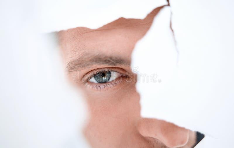 Hombre de negocios atento que mira a través de un agujero en una pared de papel foto de archivo