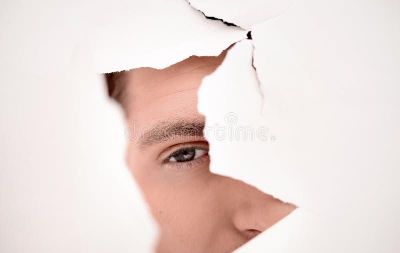 Hombre de negocios atento que mira a través de un agujero en una pared de papel foto de archivo libre de regalías