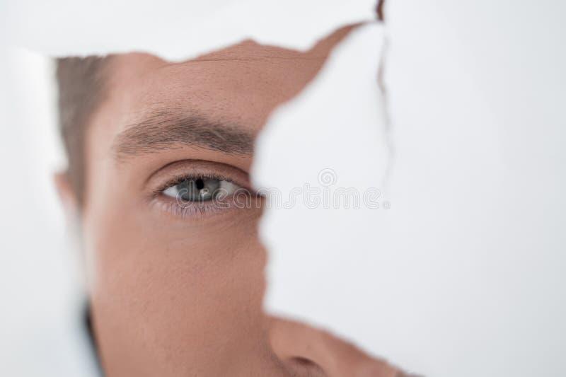 Hombre de negocios atento que mira a través de un agujero en una pared de papel fotografía de archivo libre de regalías
