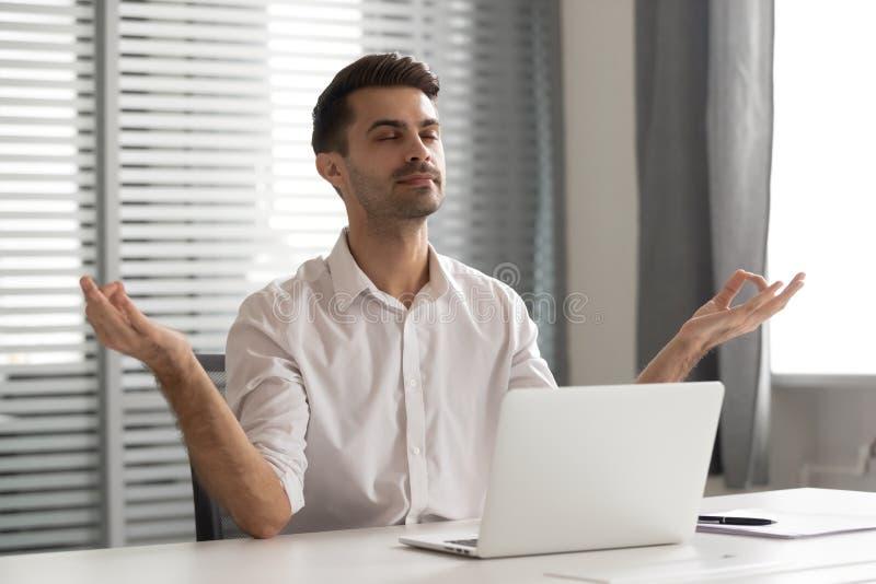 Hombre de negocios atento tranquilo que toma la rotura para meditar para sentarse en el escritorio de oficina imagen de archivo