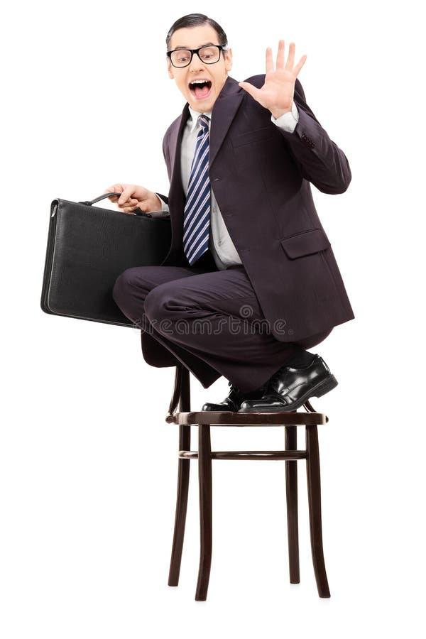 Hombre de negocios aterrorizado que sostiene la cartera que se coloca en una silla y imagenes de archivo