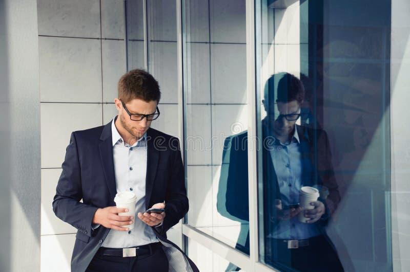 Hombre de negocios atractivo con el dispositivo y el café del teléfono en manos encendido fotos de archivo libres de regalías